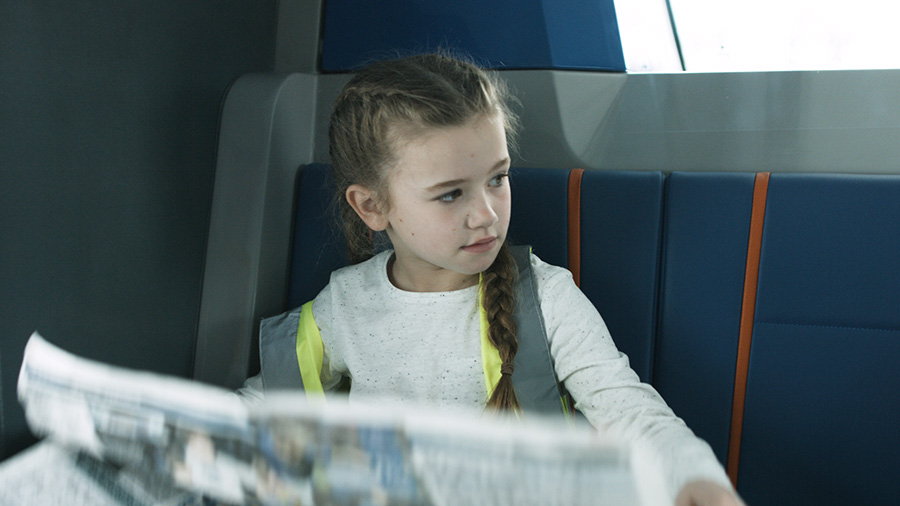 Girl reading the newspaper on the bus